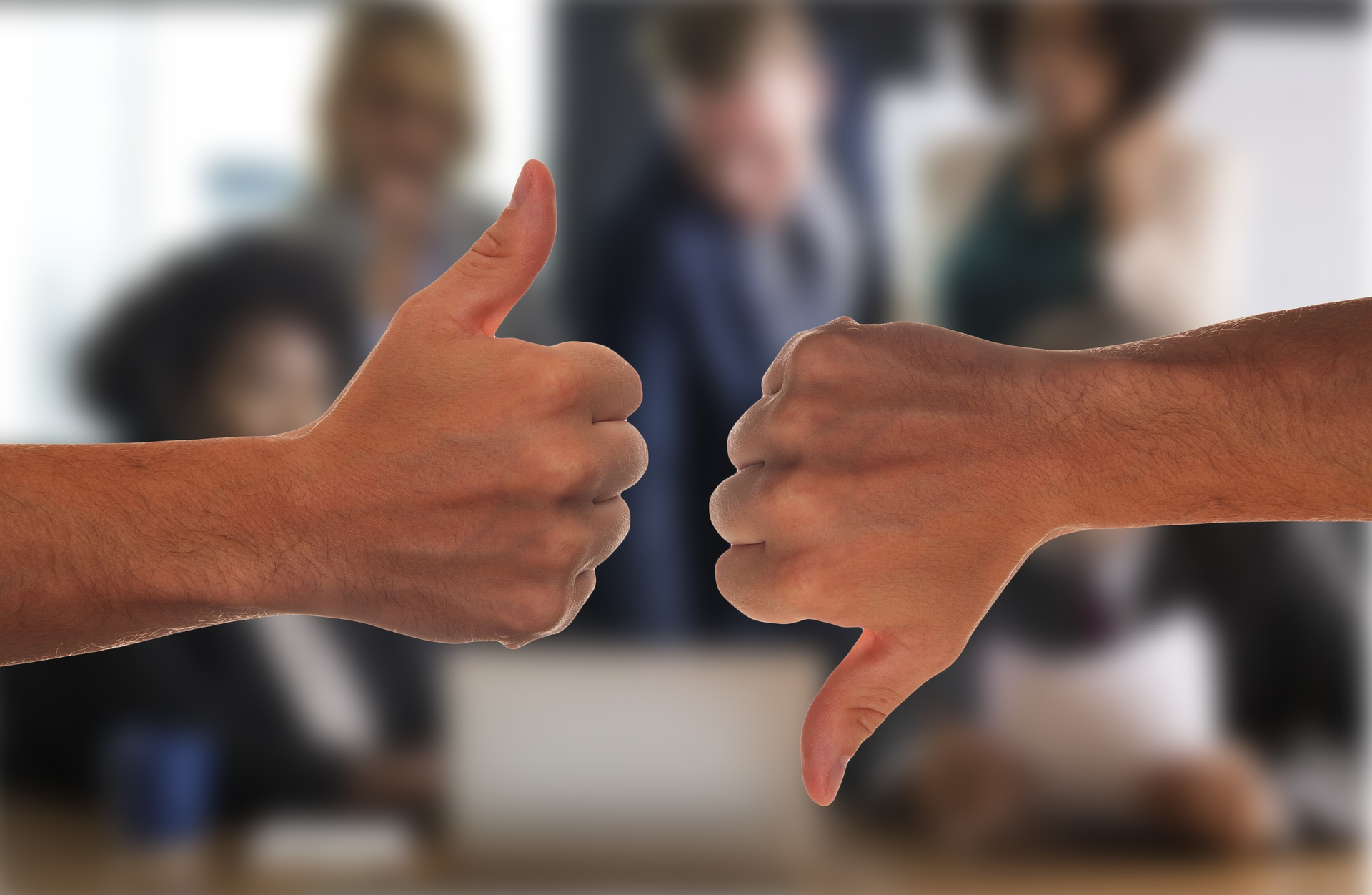Two business people showing thumbs up and down sign