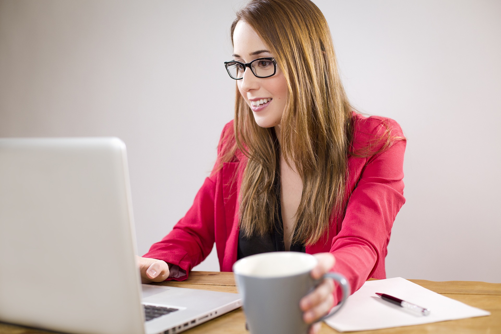 business woman wearing eye glasses and holding a cup
